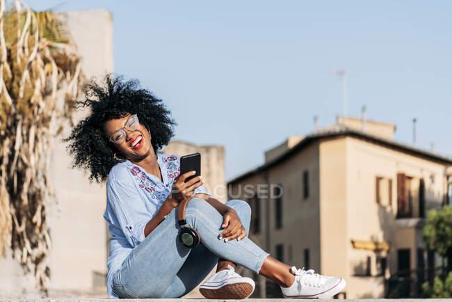 Donna ridente con capelli afro e occhiali utilizzando smartphone — Foto stock