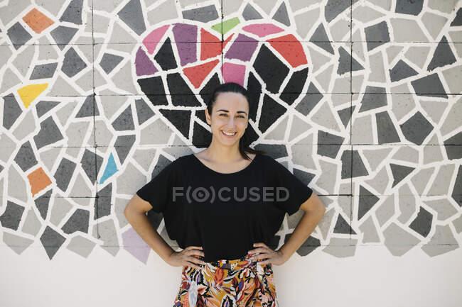 Retrato de una mujer sonriente frente a una pared colorida - foto de stock