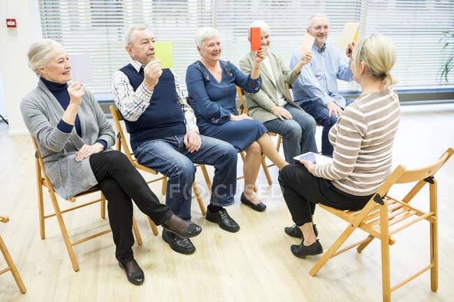 Пожилые люди в доме престарелых посещают групповую терапию с помощью разноцветных бумажных карточек — стоковое фото