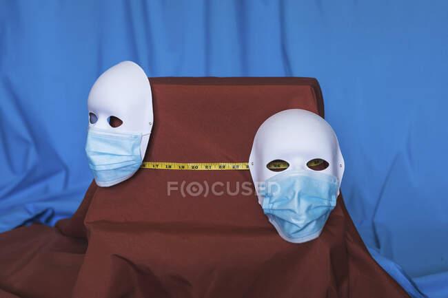 Estúdio de duas máscaras de teatro usando máscaras protetoras separadas por fita métrica — Fotografia de Stock