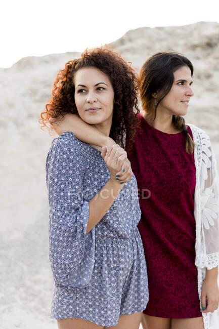 Jovens mulheres atenciosas em pé no campo durante o dia ensolarado — Fotografia de Stock