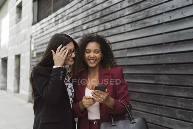 Souriant jeunes collègues d'affaires multiethniques partageant un téléphone intelligent contre un mur dans la ville — Photo de stock