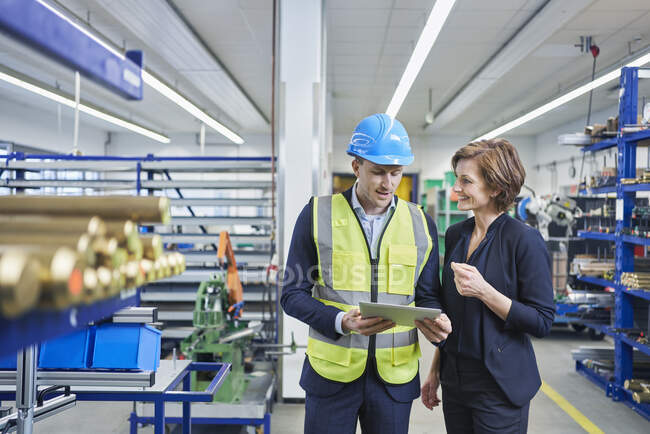 Supervisor and female manager discussing over digital tablet in industry — Stock Photo