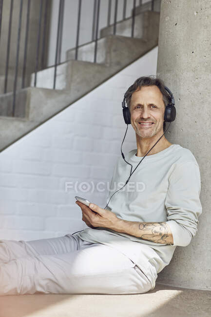 Hombre mayor sonriente con auriculares escuchando música en un apartamento loft - foto de stock