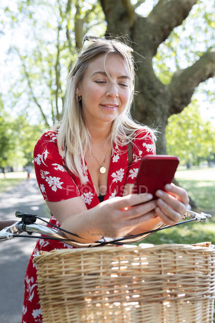 Beautiful woman using smart phone while leaning on bicycle at public park — Stock Photo
