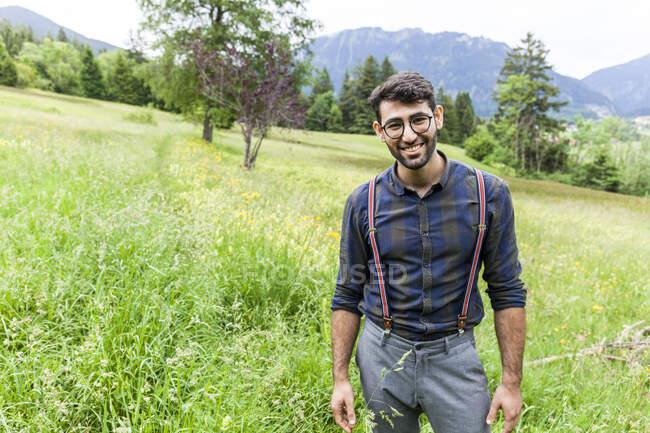 Porträt eines lächelnden jungen Mannes auf einer Wiese, Reichenwies, Oberammergau, Deutschland — Stockfoto
