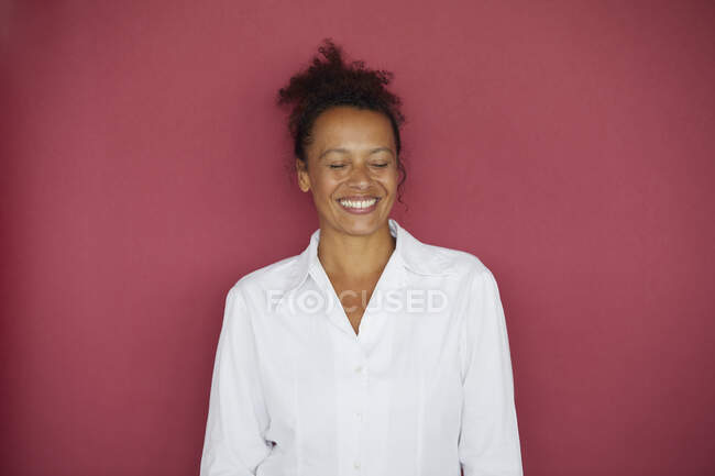 Portrait of smiling businesswoman with eyes closed against red background — Stock Photo
