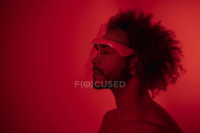 Hombre joven con los ojos cerrados usando máscara de luz led roja contra la pared en casa - foto de stock
