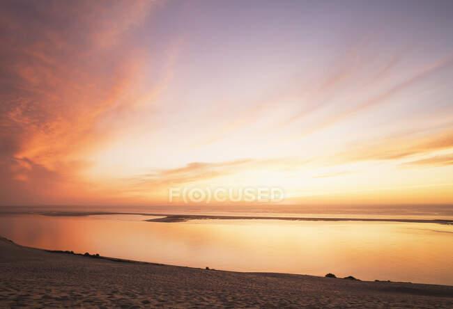 Vista idílica de la luz del sol que refleja en el océano Atlántico contra el cielo al atardecer, Duna de Pilat, Nueva Aquitania, Francia - foto de stock