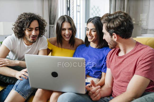 Amici multietnici sorridenti che condividono laptop mentre sono seduti in salotto — Foto stock
