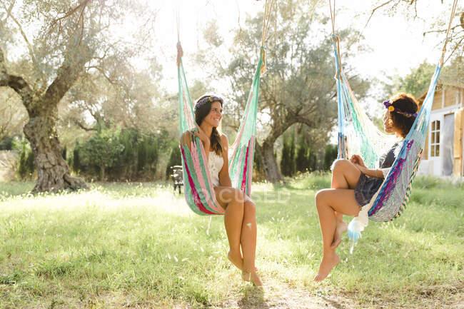 Glückliche junge Frauen reden, während sie in Hängematten auf dem Hof sitzen — Stockfoto