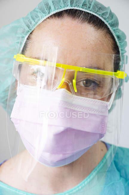 Close-up do dentista feminino usando máscara e óculos na clínica — Fotografia de Stock