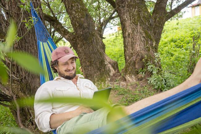 Человек отдыхает на гамаке в лесу — стоковое фото