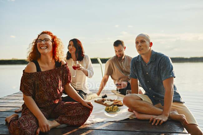 Щасливі друзі, які влаштовують пікнік на пристані біля озера на заході сонця. — стокове фото