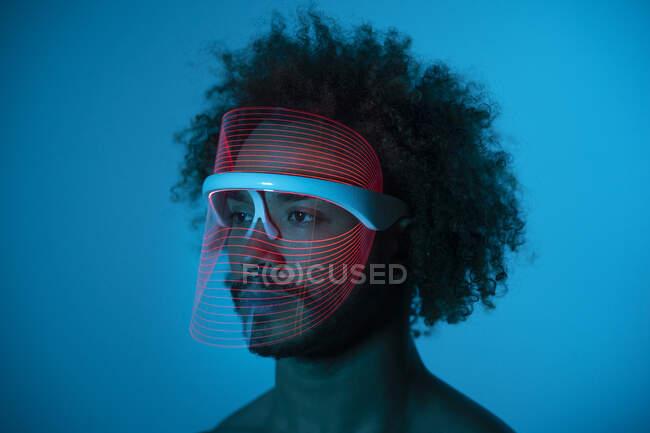 Hombre joven con máscara led roja mirando hacia la pared en casa - foto de stock