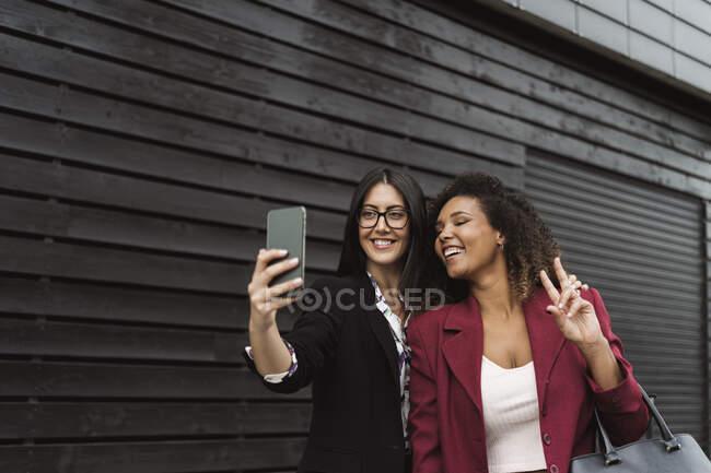 Belle femme d'affaires prenant selfie avec une collègue féminine en ville — Photo de stock
