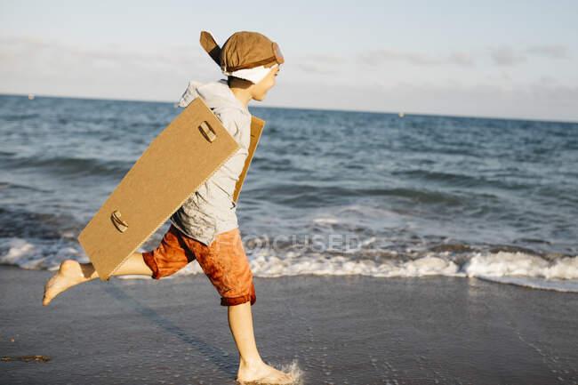 Niño con gorra de aviador y alas de cartón corriendo en la playa - foto de stock