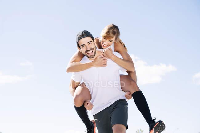 Hombre alegre piggybacking mujer mientras camina contra el cielo durante el día soleado - foto de stock