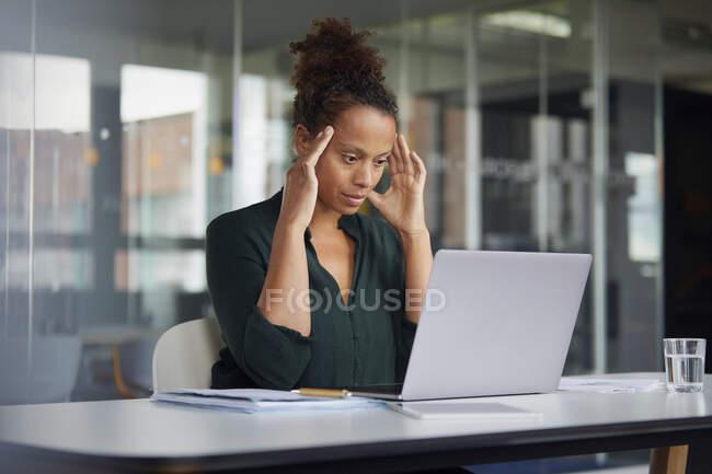 Retrato de empresaria pensativa en el escritorio mirando el portátil - foto de stock