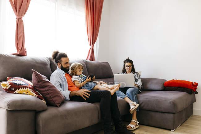 Mujer trabajando sobre el ordenador portátil, mientras que el padre y la hija utilizando el teléfono inteligente en el sofá en casa - foto de stock