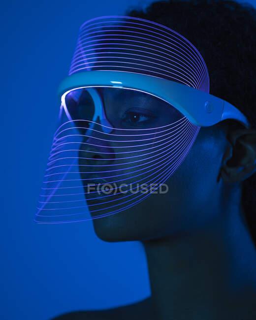 Primer plano de la mujer joven con máscara led azul contra la pared en casa - foto de stock
