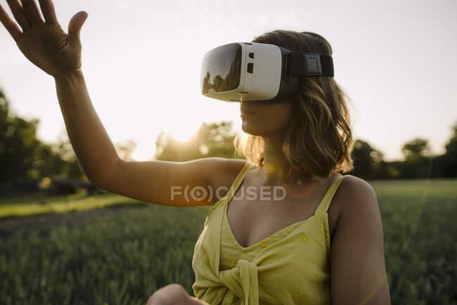 Jovem mulher vestindo óculos VR em um campo de grãos no campo — Fotografia de Stock