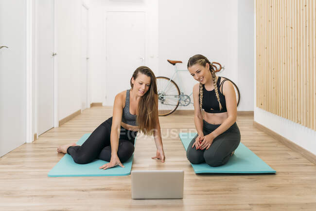 Two sporty women having an online course at health club — стоковое фото