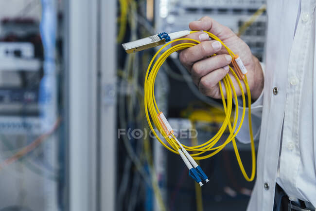 Close-up of mature man holding yellow cables in data center — Stockfoto