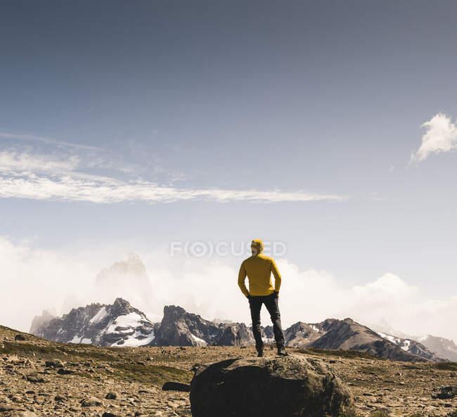 Чоловік, який подорожує садом проти неба, стоячи на скелі (Патагонія, Аргентина). — стокове фото