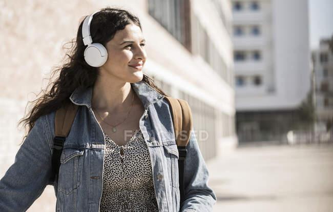 Молодая женщина слушает музыку через наушники, глядя в сторону, стоя в городе — стоковое фото