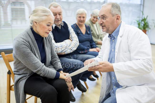 Группа пожилых людей, посещающих консультации в доме престарелых — стоковое фото