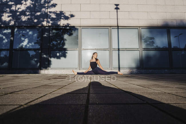 Молодая женщина практикует сплиты на улице в городе — стоковое фото