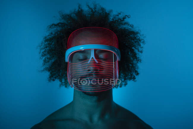 Joven con los ojos cerrados usando máscara led roja contra la pared en casa - foto de stock