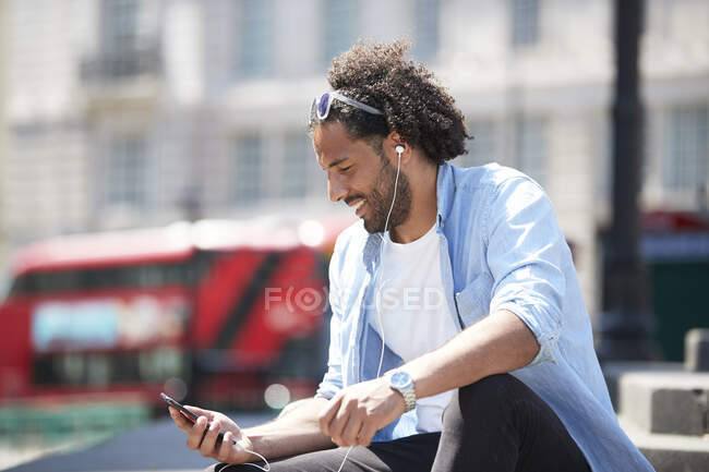 Portrait of smiling young man sitting outdoors listening music with cell phone and earphones, London, UK — Foto stock