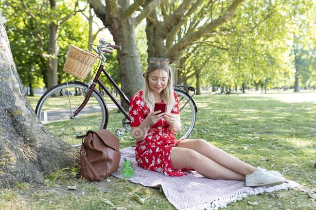 Frau benutzt Smartphone im öffentlichen Park — Stockfoto