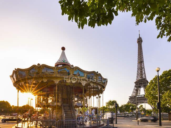 Карусель и Эйфелева башня на фоне ясного неба на восходе солнца, Париж, Франция — стоковое фото