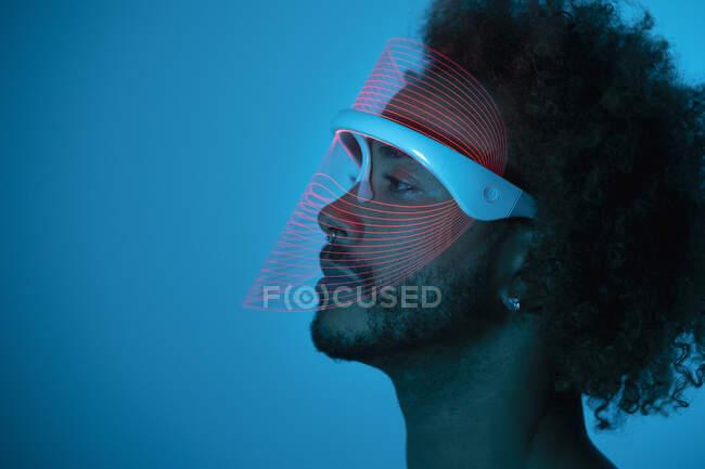 Pensativo joven con máscara led roja contra la pared en casa - foto de stock