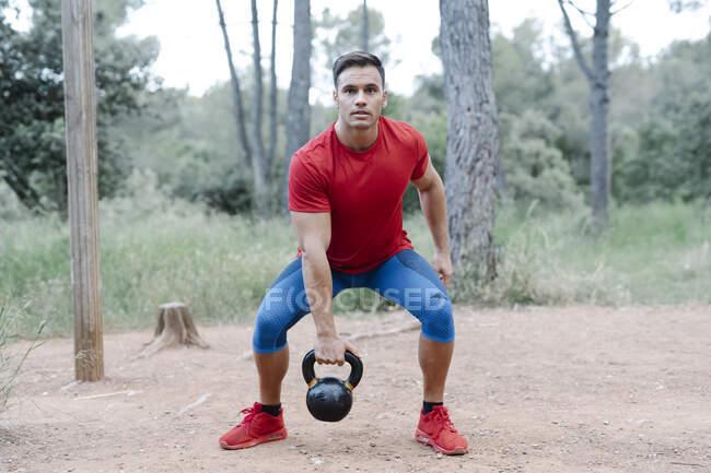 Молодий атлетичний чоловік з бараниною в лісі. — стокове фото