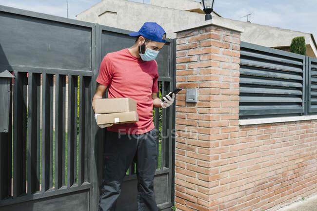 Мужчина почтовый работник с помощью мобильного телефона, стоя с пакетом против ворот — стоковое фото