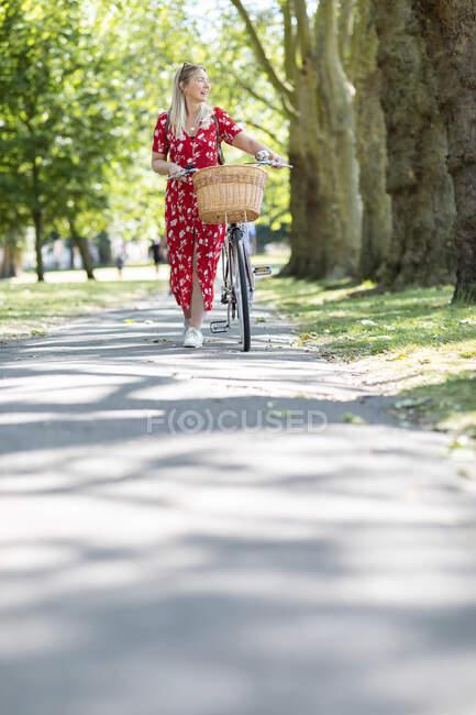 Mujer mirando hacia otro lado mientras camina con bicicleta en el sendero en el parque público durante el día soleado - foto de stock