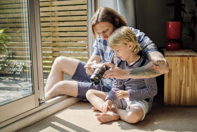 Padre e hijo viendo la cámara SLR mientras están sentados junto a la ventana en casa - foto de stock