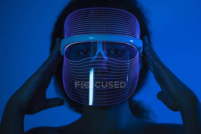 Primer plano de la mujer con máscara led azul contra la pared en casa - foto de stock