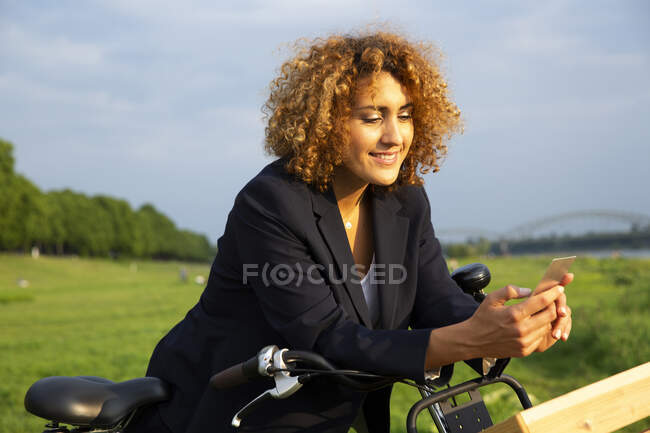 Smiling businesswoman with curly hair using smart phone while standing with bicycle against sky — Foto stock