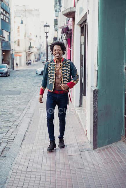 Feliz hipster masculino em casaco retro andando na calçada durante o dia ensolarado — Fotografia de Stock