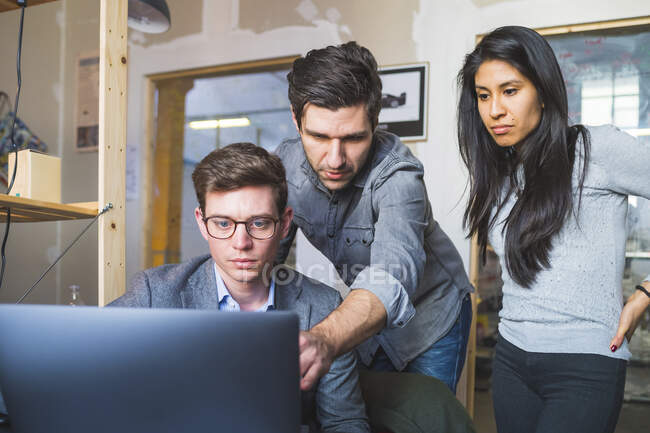 Three business people sharing laptop at desk in office — Stock Photo