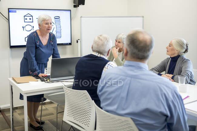 Старший инструктор проводит курсы по хранению булыжников для пожилых людей — стоковое фото