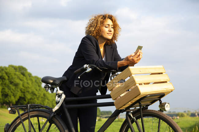 Businesswoman using smart phone while standing with bicycle against sky — стоковое фото