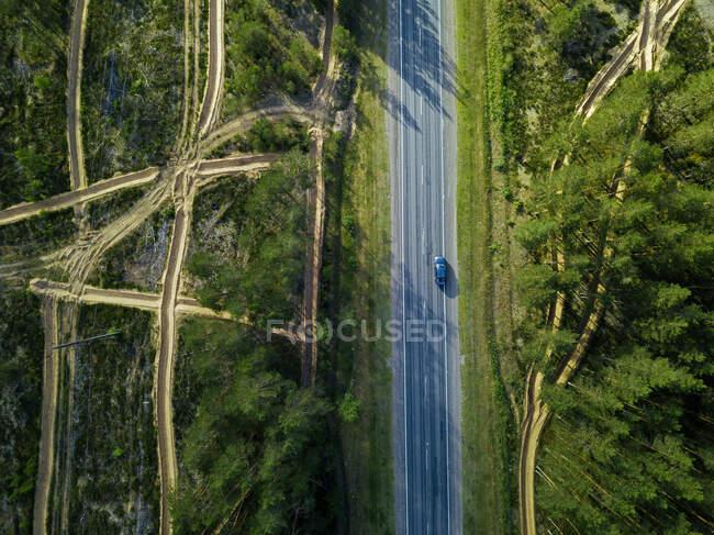 Vista aérea de la carretera a través del bosque en un hermoso río verde, tiro drone superior. - foto de stock