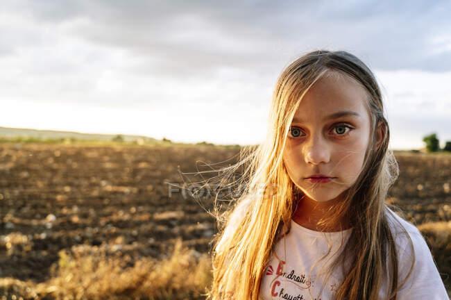 Девочка-подросток с длинными светлыми волосами, стоящими на фоне неба на закате — стоковое фото