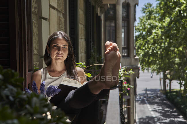 Woman with book sitting in balcony during weekend — Stock Photo